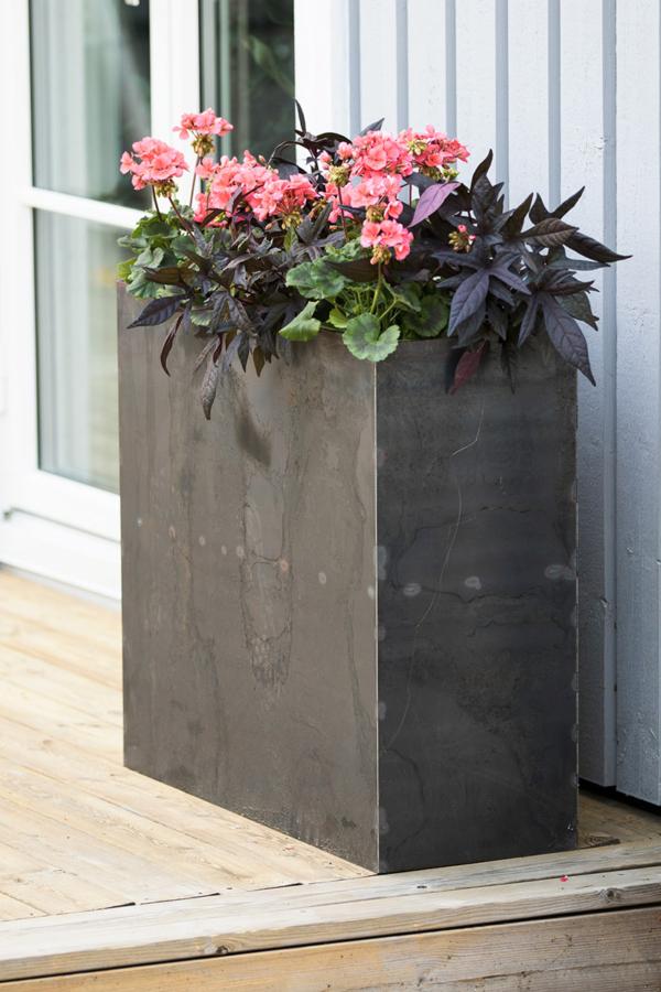 Hög odlingslåda i cortenstål med blommor